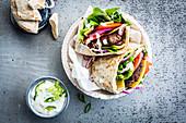 Pita-Burger mit Tomaten, Zwiebeln und Salat  dazu Tzatziki