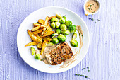 Pork steak with mustard sauce, fries and Brussels sprouts