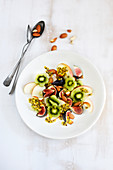 Obstsalat mit Apfel, Kiwi, Feige, Passionsfrucht und Mandeln