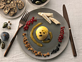Mangosorbet in Olivenöl und schwarzen Olivenbrotchips