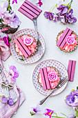 Rosa Torteletts mit Cremefüllung, Ruby-Schokoriegeln und Rosenblüten