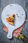 Ein Stück Pizza mit Huhn, Oliven und Gemüse