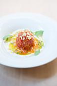 Glasierte Tomate mit Paprikasauce, Mandeln und Kräutern