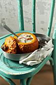 Kürbissuppe mit Garnelen serviert in ausgehöhltem Kürbis