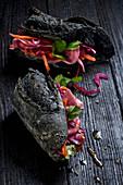Schwarzes Aktivkohle-Sandwich mit Gemüse