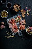 Vorspeisenplatte mit Schinken, Salami, Oliven, Brot- und Gemüsechips