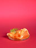 Räucherlachs auf Teller vor pinkfarbenem Hintergrund