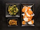 Chinesisches Gericht mit Fleisch und Gemüsebeilagen auf seperaten Tellern