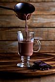 Heiße Schokolade wird aus Topf in Glas-Henkelbecher gegossen