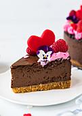 Ein Stück Schokoladen-Käsekuchen dekoriert mit Herz, Himbeeren und Blüte