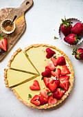 Zitronentarte dekoriert mit herzförmigen Erdbeeren