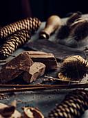 Herbstliches Stillleben mit Schokolade, Nüssen und Zapfen