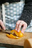 Frau schneidet gelbe Paprikaschote in Streifen