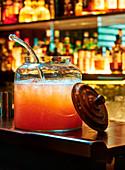 Cocktail 'American Flyer' in großem Glasgefäß auf Bartheke