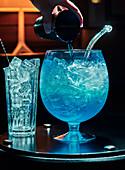 Blauen Cocktail in großem Glasgefäß zubereiten
