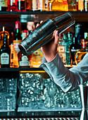Barkeeper bereitet Cocktail in einem Shaker vor