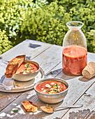 Mediterrane Gazpacho mit Feta auf sommerlichem Gartentisch