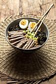 Ramen mit Algen, Ei, Frühlingszwiebeln und Rindfleisch im Schälchen (Japan)