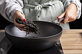 Getrocknete Seealgen zum Kochen in die Pfanne geben