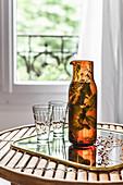 Detox-Wasser mit Kräutern in Karaffe auf Spiegeltablett
