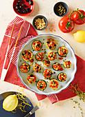 Zucchini-Häppchen mit Tomatenwürfeln, Oliven und Pinienkernen