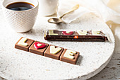 Belgische Milchschokolade mit der Aufschrift 'love' zur Tasse Kaffee
