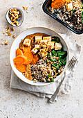 Quinoa-Bowl mit Tofu, Karotten, Spinat und Erdnusssauce