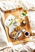 Gefülltes Brötchen mit Ei dazu Kaffee und Blumen auf Frühstückstablett