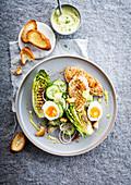 Caesar Salat mit Hühnerbrust, gegrillten Salatherzen, Ei, Gurke und Joghurtsauce