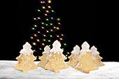 Weihnachtlicher Plätzchen-'Wald', im Hintergrund leuchtender Weihnachtsbaum