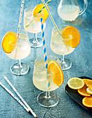 Champagner-Cocktail mit Orangenscheiben und Strohhalmen