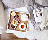 Tablett mit Tee, Gebäck und Kerze auf Sofa