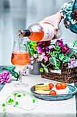 Ein Glas Roséwein und Ziegenkäse mit Cracker und Kirschtomaten zum Aperitif