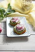 Gelbe Tomatenscheibe belegt mit Guacamole und Rettich