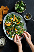 A salad of roasted squash, with kale, spinach, arugula, feta cheese, chopped pistachios, and a lemon and olive oil vinaigrette