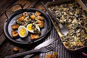 Mangoldauflauf serviert mit Croutons und hartgekochten Eiern