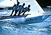 Three young men on sailing boat at sailing competition, Chiemsee, Bavaria, Germany