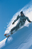 Snowboarder in powder snow, snowboarding down a slope, Winter Sports