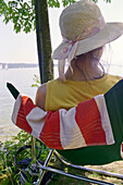 Young woman with sun shade in deck chair, Starnberger See, Bavaria, Germany