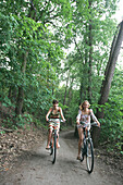 Two young woman cycling in wood, Berlin, Germany