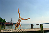 Young woman do handstand on jetty, Starnberger See, Bavaria, Germany