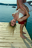 Young couple having fun on a jetty, Starnberger See, Bavaria, Germany