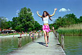 Young woman jumping on a jetty, Starnberger See, Bavaria, Germany