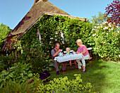 Grandparents & grandson in garden idyll, Hollaender Hof in Wagersrott Schleswig-Holstein, Germany Location aus der Fernsehserie Der Landarzt Wohnsitz des Kraeuterdoktors