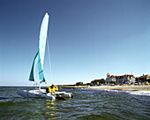 Catamaran before beach of seaside resort Kuehlungsborn, Baltic Sea, Germany