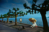 One woman sitting under a umbrella, Boardwalk of Meersburg, Lake of Constance, Germany
