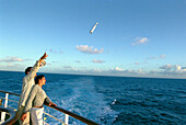 Young couple throwing message in a bottle into the sea, Cruise ship Aida, Caribbean, America