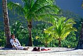 Young couple lying at Maracas Bay, Trinidad, Caribbean