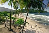 People walking along Maracas Bay, Trinidad, Caribbean