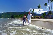 Young couple running at Maracas Bay, Trinidad, Caribbean